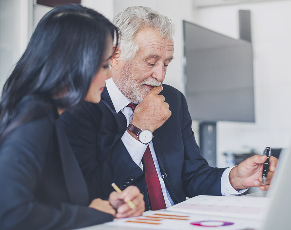 Older broker coaching woman agent while looking at stats